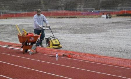 A worker smooths the surface at Kingston Stadium. Field Turf will be placed on the rock. (Photo by Jeff Linder)