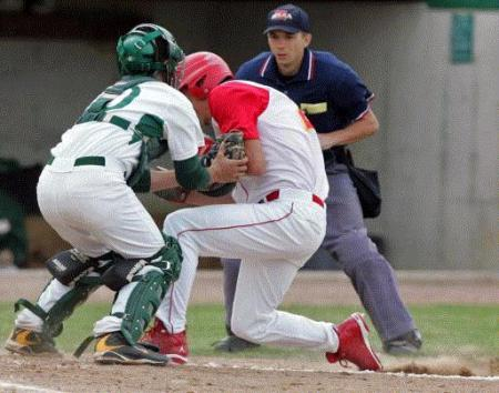 Cedar Rapids Kennedy catcher Sam Hunter (left) braces for contact as Marion's Dusty Albaugh goes in hard during the Bob Vrbicek Metro Baseball Tournament Monday at Kennedy. Hunter didn't have the ball, but Albaugh was called out and ejected on the play. (Photo by Chris Macklin)