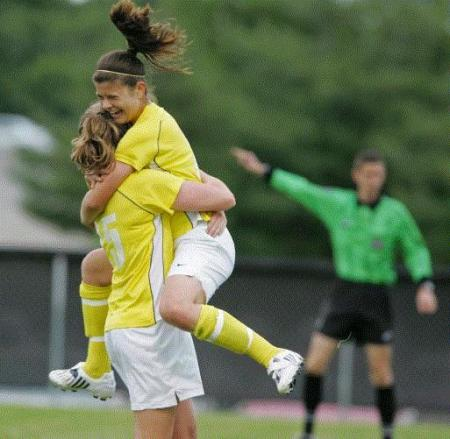 Hannah Palomo jumps into the arms of teammate Katherine Lewis after scoring one of her two second-half goals in Cedar Rapids Kennedy's 4-1 win over Cedar Rapids Washington in a Class 2A girls' regional soccer match Monday at Kennedy. (Photo by Chris Macklin)