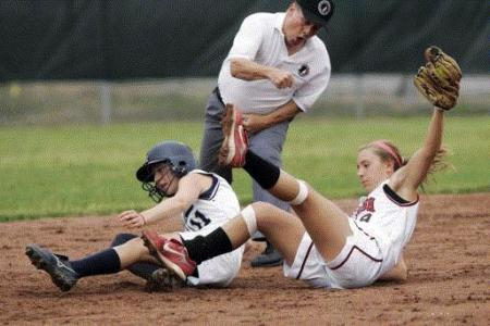 Iowa City High shortstop Molly Prybil (right) tags out Cedar Rapids Xavier baserunner Kelsey Kuba-Tresnak in a softball game Tuesday at Bob Erusha Field. The Saints swept the MVC double-header, 2-1 and 5-1. (Photo by Liz Martin)